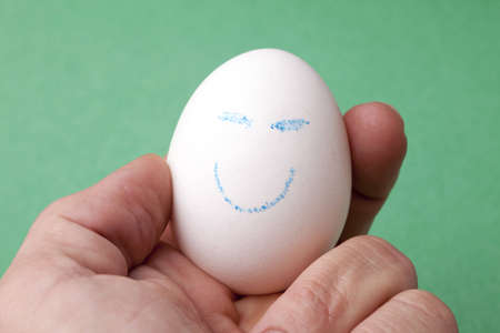 An egg decorated in blue crayon with a happy smiley face. 版權商用圖片