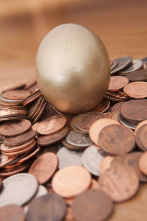 Golden egg nested on pile of coins Stok Fotoğraf