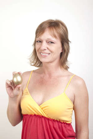 An adult female in a sundress showing her golden egg