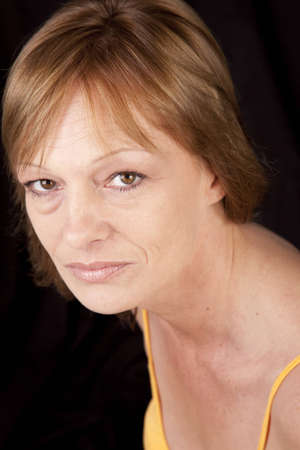 Portrait of a mature adult woman on a black background. 版權商用圖片