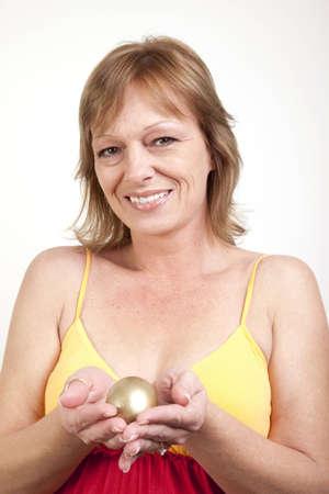 cradling: A mature woman cradling her golden egg in her hands