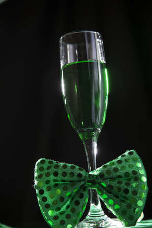 A wine glass with a green beverage at a party for st patricks day.