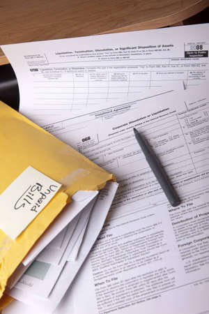dissolution: Unpaid bills in a yellow envelope on a stack of tax forms for corporate dissolution on a desk.