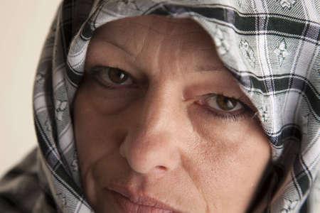 Mature adult woman in a mideast style headdress veil. 版權商用圖片