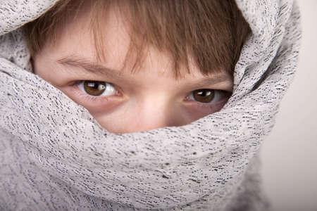 Closeup of eyes of a boy in an asian tribal headdress 版權商用圖片