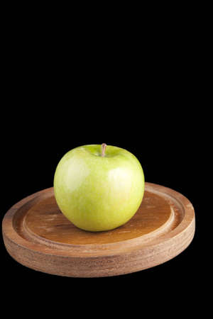 Green granny smith apple on a wooden platter isolated on black.