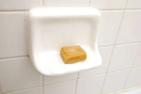 A bar of old fashioned soap sitting on a soapdish.
