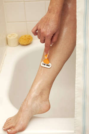 Closeup of female shaving her leg in the shower Stock Photo