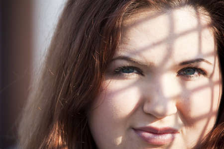 Closeup face portrait of a young overweight woman with interesting shadows from a fence.