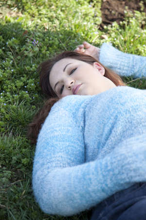 woman laying: An overweight woman laying in a field of grass