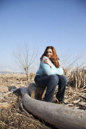 An overweight woman sitting on a stump in a field of dead vegetation