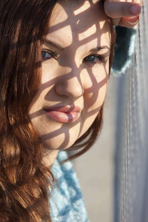 A woman leaning against a checkered fence with morning sunlight creating a pattern of shadow on her face. Stock Photo