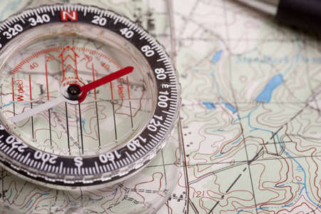 A compass on a topographical map showing terrain features