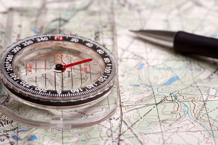 A compass alongside a road on a map with a pencil Stock Photo
