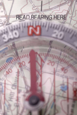 Closeup of a compass on a map, focused on where to read bearing.