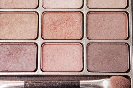 Multiple shades of eye shadow with a brush and loose powder flakes Stock Photo
