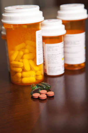 dosage: Pill bottles on a table with an assortment of pills in front of them for daily dosage.