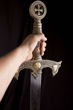knights templar: Arm holding out a knights ornate sword in a dramatic dark scene