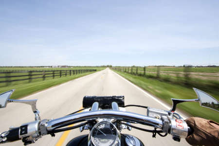 Shot from rider perspective of a motorcycle cruising down a small country lane.