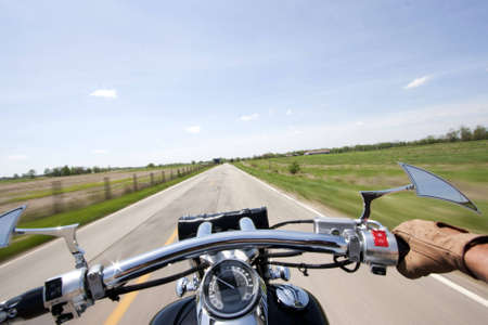 Shot from rider perspective of a motorcycle traveling down a country road on a sunny day Stock Photo