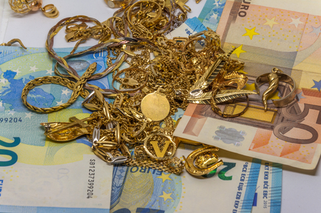 Old gold on euro bills, cash for gold store concept Banco de Imagens