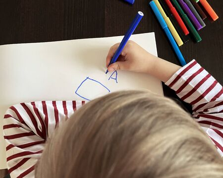 Small boy draws at the table. Top view, felt-tip pens of different colors are on the table