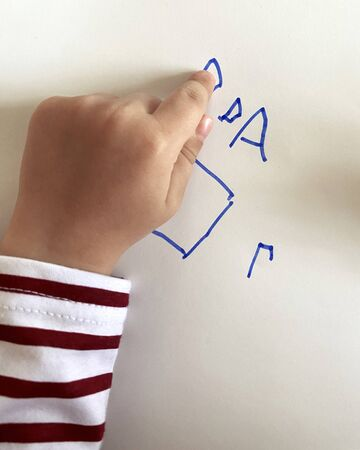 Small boy's hand hand pointing to drawns. Top view