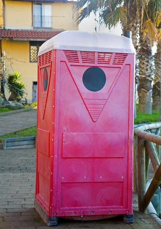 View of a red and white Portable toilette