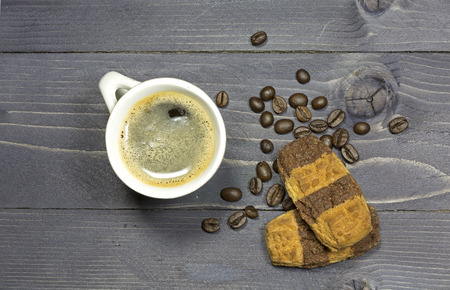 coffeebeans: Cup of coffee and coffeebeans with double colored cookies on wooden background