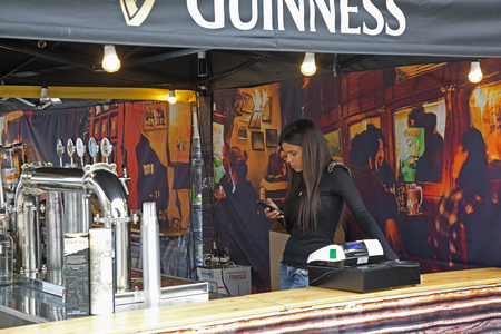 international beer: Naples, Italy. April 21, 2016: Brazilian girl using smartphone inside the Guiness Beer stand at the Naples International Street Food Festival in the Business Centre. Editorial