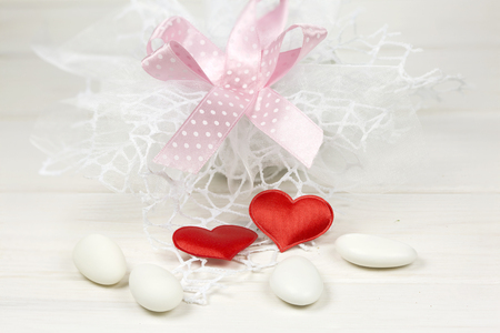 favour: Candy favour red hearts and sugared almonds on blue-gray wooden background