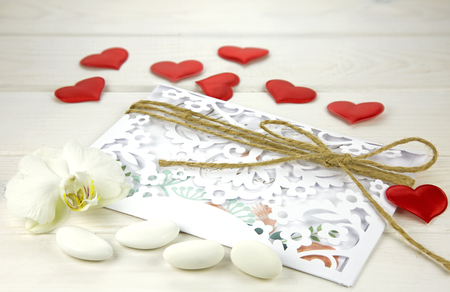 sugared almonds: Wedding card with sweets and sugared almonds on white wooden background