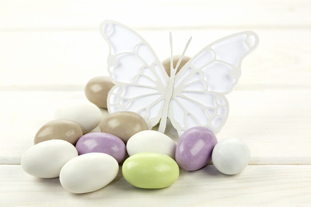 sugared almonds: Colored sugared almonds and papery butterfly on white wooden background