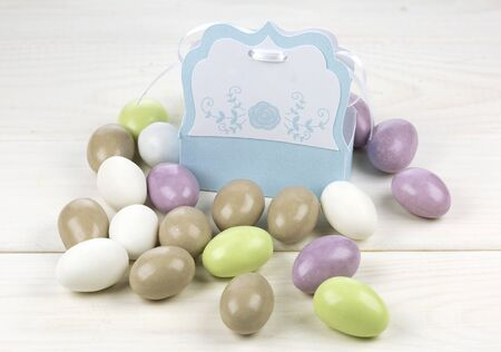 Colored sugared almonds and papery box on white wooden background
