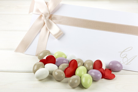 sugared almonds: Colored sugared almonds, red heart shaped confetti and wedding paper on white wooden background Stock Photo