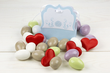 papery: Colored sugared almonds red heart shaped confetti and papery box on white wooden background
