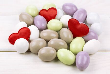 sugared almonds: Sugared almonds with red heart shaped confetti on white wooden background