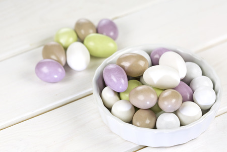 Colorful sugared almonds on wooden white background Stock Photo