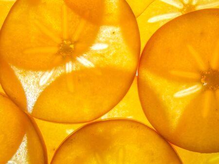 ebenaceae: background of back lit ripe kaki persimon slices arranged Stock Photo