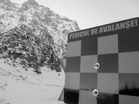 hazardous area sign: avalanche sign written in romanian in a hazardous area
