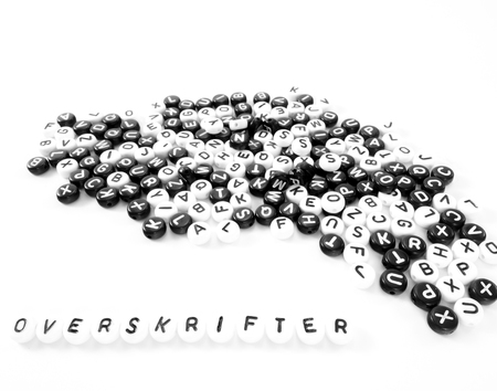 heap of round letters black and white and headlines word written in danish; overskrifter
