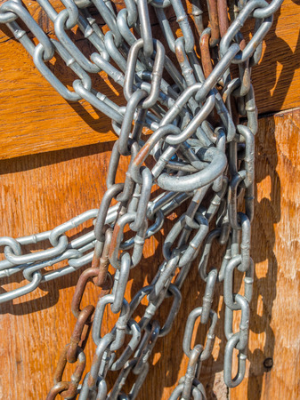 restraint: tangled chains near wooden bridge abstract photo