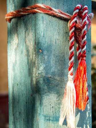 red and white martisor cord tied to house pole