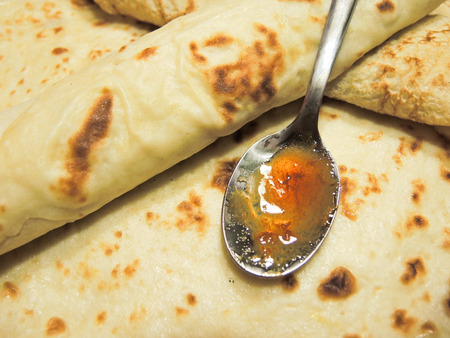 delicious crepes filled with jam and teaspoon Stock Photo