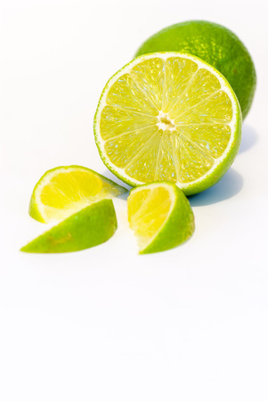 lemon wedge: whole lime half lime and lime slices over white background with copy space