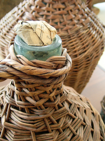 glass demijohn wrapped in straw basket traditional alcohol different liquids storage