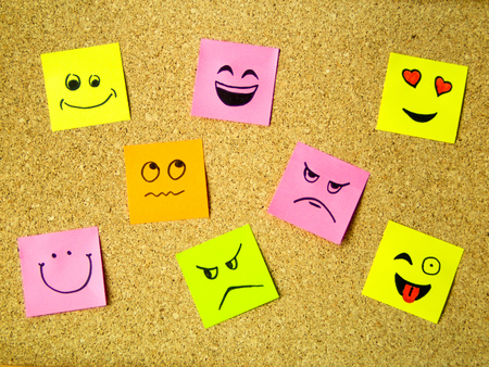 cork board with colorful sticky notes  representing various emoticons with various emotions communication concept