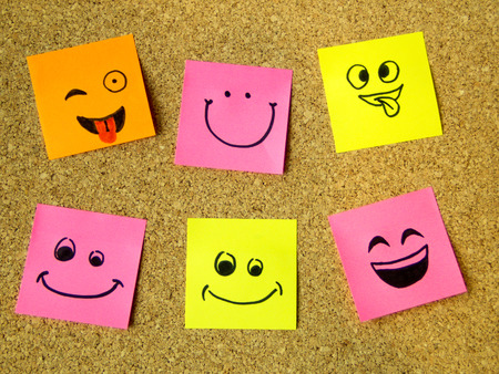 cork board with colorful post its representing various emoticons with various emotions communication concept