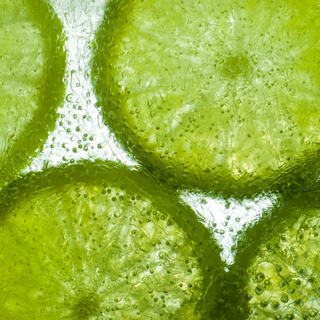 fresh lime slices frozen in translucent ice with back lit abstract texture photo