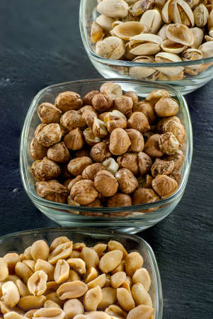 bowls with assorted nuts like hazelnuts pistachio and peanuts on black slate healthy life concept